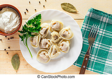 Plate with boiled dumplings served with parsley and sour cream
