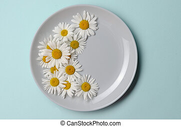 plate with chamomile flowers on blue background