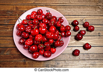 Plate with cherries on wooden table