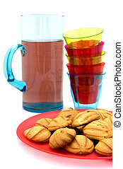 Plate with cookies, stack of glasses and carafe with lemonade