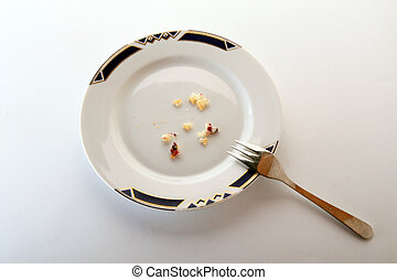 An arrangement of a white dessert plate with fork and crumbs, isolated on a white background.