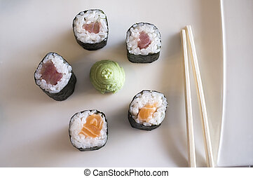 Plate with five makizushi pieces, wasabi sauce and sticks....