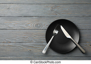 Plate with fork and knife on wooden background, top view