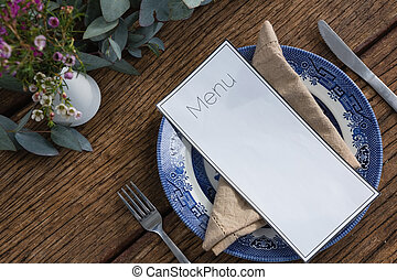 """""""Plate with fork, butter knife, napkin and menu card on wooden table"""""""