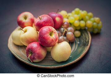 Plate with fresh autumnal fruits. apples in selective focus