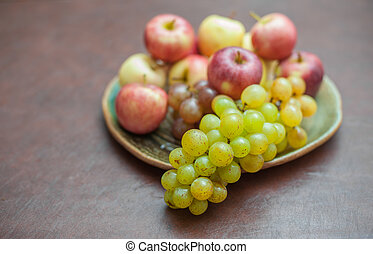 Plate with fresh autumnal fruits. grapes in selective focus