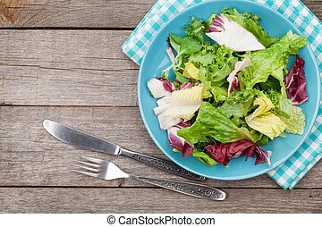 Plate with fresh salad, knife and fork. Diet food