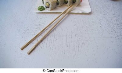 Plate with Fresh Sushi Rolls in a Japanese Restaurant on a Stylish White Wooden Table. Dolly Shot