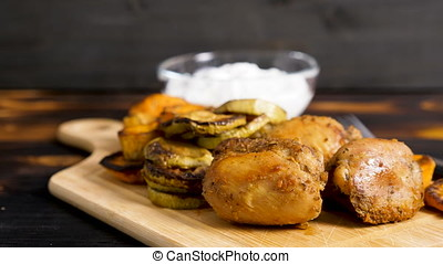 Plate with fried chicken and grilled vegetables. Zucchini...
