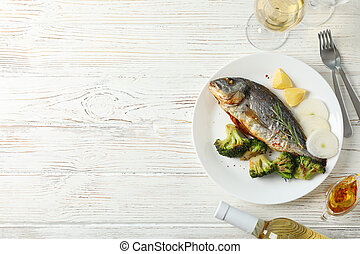 Plate with fried Dorado fish on garnished wooden background, top view