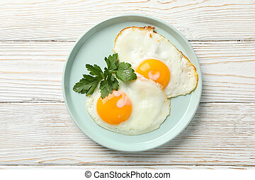 Plate with fried eggs on wooden background, top view