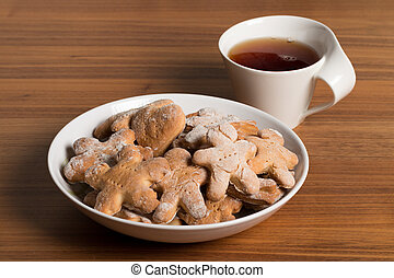 Plate with handmade cookies. Cup of tea on a wooden table