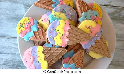 Plate with ice cream cone cookies. Tasty glazed biscuits,...