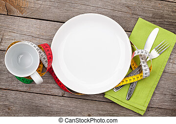 Plate with measure tape, cup, knife and fork. Diet food on...
