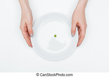 Plate with one green pea holded by hands of woman