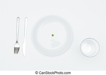 Plate with one pea, glass of water, fork and knife