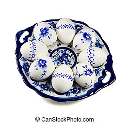 Plate with painted Easter eggs on white background