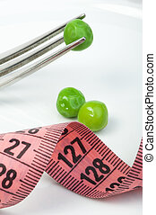 Plate with peas and centimeter measure close up.