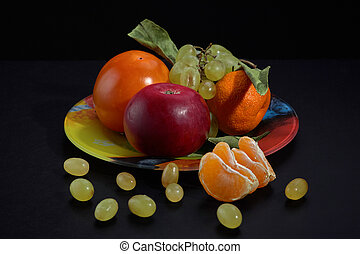 Plate with persimmon apple grapes and tangerine on a black background, close-up