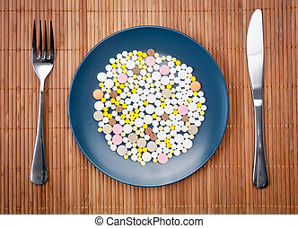 Plate with pills fork and knife on bamboo mat