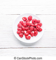 Plate with raspberries on white wooden table.