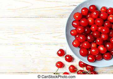 Plate with red cherry on white wooden background, top view