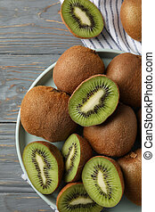 Plate with ripe kiwi on wooden background, top view
