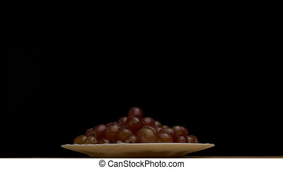 Plate with rotating frozen grapes, close-up, slow motion, copy space