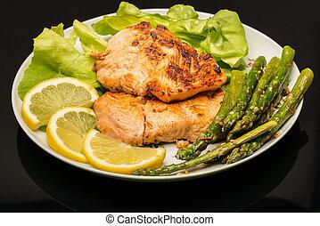 Plate with salmon, asparagus, salad and lemon