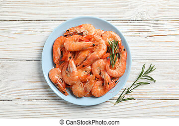Plate with shrimps on wooden background, top view