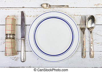 plate with silver cutlery on an old table