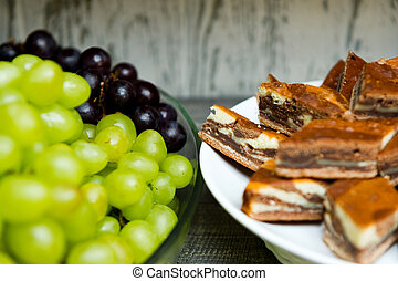 plate with sliced pie and plate with grapes close-up