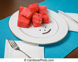 Plate with slices of ripe watermelon on a wooden table