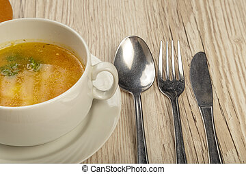 Plate with soup and cutlery on a wooden background.