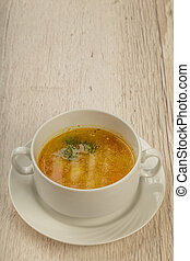 Plate with soup in a white plate on a wooden background.