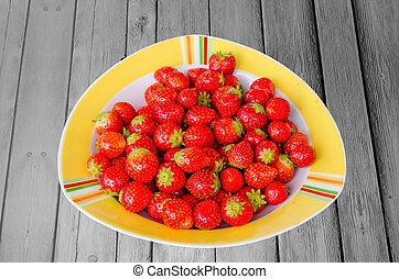 Plate with strawberries on wooden base