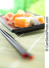 Plate with sushi and chopsticks, isolated on white