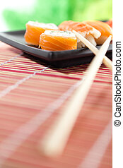 Plate with sushi and chopsticks, isolated on white on white