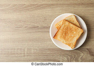 Plate with toasts on wooden background, top view