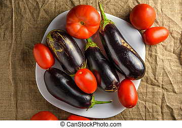 Plate with vegetables - eggplants and tomatoes. Top view