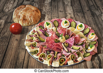 Plateful of Serbian Appetizer Meze with Pita Bread and Tomato on very old Wooden Table