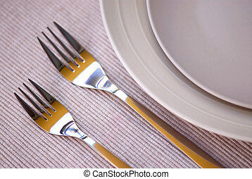 Dinner place setting with plates and cutlery shallow dof