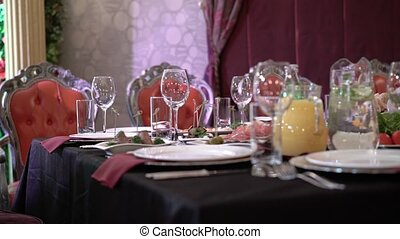 Plates and glasses on red napkin in restaurant at the party