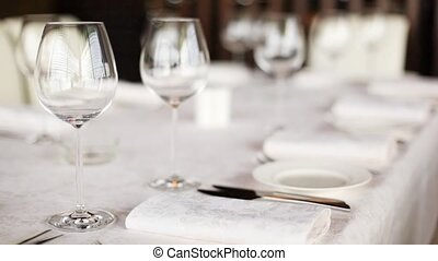 Plates, knifes and wineglasses for wine stand on table