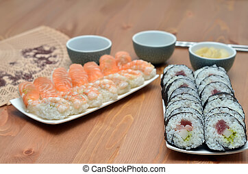 plates of maki sushi rolls and nigiri sushi with salmon and...