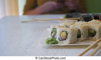 Plates of Sushi Rolls in a Japanese Restaurant on a White Stylish Wooden Table. Dolly Shot