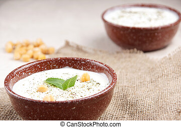 Plates of Turkish soup with chickpeas and mint on the table, decor in a rustic style