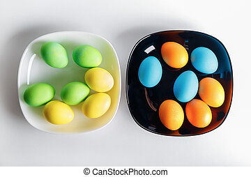 Easter eggs on a black and white plates. Top view.