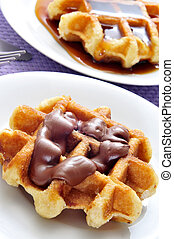 waffles - plates with waffles with chocolate and syrup on a ...