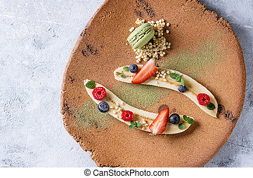 Food plating dessert organic banana with fresh berries, mint, puffed rice and macaroon biscuit served with green tea matcha powder on terracotta plate over gray texture background. Flat lay, space